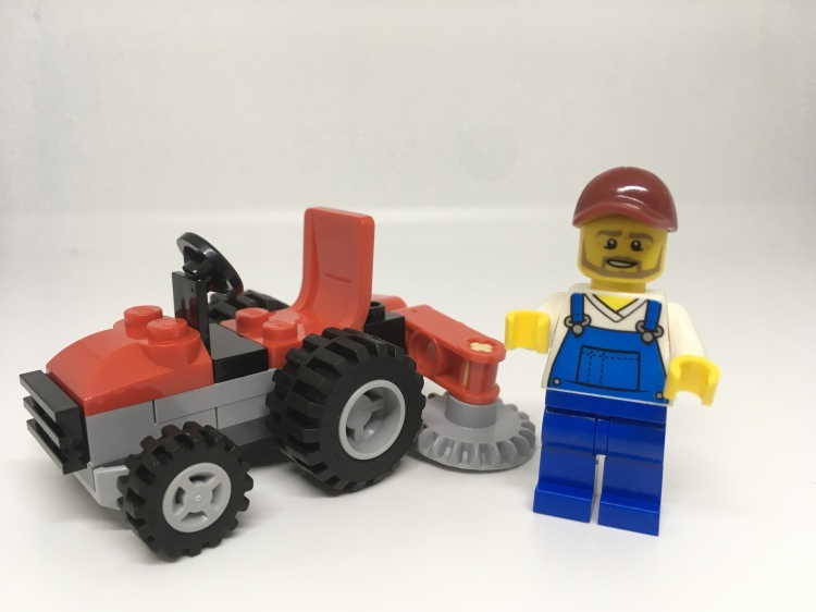 LEGO gardener minifigure with tractor lawnmower